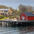 Traditional Norwegian red wooden fishing boat barn on the sea coast in spring — Stock Photo
