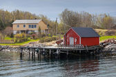 Traditional Norwegian red wooden fishing boat barn on the sea coast in spring — Stockfoto