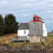 Foto Stock: Old NorwegiLighthouse with red top on seacoast