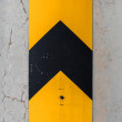 Vertical caution striped yellow and black sign on concrete column — Stock Photo #25929131