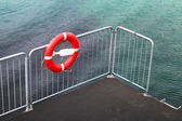 Lifebuoy on the metal railing of small pier with bright sea water on a background — Stock Photo