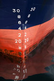 Bow of the cargo ship with red waterline and draft scale numbering — Stock Photo