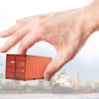 Bright red metal freight shipping container in man's hand above port backgroun — Stock Photo