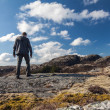 Young man goes on the rock and looks over horizon — Stock Photo