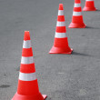 Four striped orange cones stand on gray asphalt road — Stock Photo #26247447