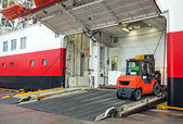 Lift truck unloads big passenger ferry through opened side ramp — Stock Photo