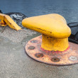 Yellow mooring bollard on concrete pier — Stock Photo