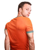 Muscular young man in orange t-shirt turns isolated on white background — Stock Photo