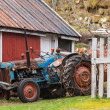 Foto Stock: Old farm tractor stands in Norwegivillage nearby red wooden house