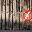 Red lifebuoy with rope on metal railings above weathered wooden wall in port — Stock Photo #27036093