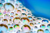 Shining colorful soap bubbles on the water — Stock Photo