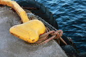 Yellow mooring bollard with blue naval rope and chain on the pier — Stock Photo