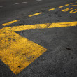 Yellow bus stop marking on dark asphalt road — Stock Photo