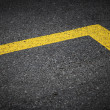 Road marking with yellow lines on dark asphalt — Stock Photo