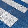 Stock Photo: Pedestricrossing road marking with white lines on dark asphalt