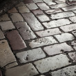 Old shining stone pavement on dark street — Stock Photo