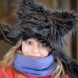 Little blond girl in fun artificial fur hat. Closeup portrait — Stock Photo