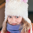 Stock Photo: Little blond girl in fun white artificial fur hat. Closeup outdoor portrait