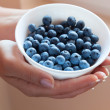 Bowl of blueberries in woman's hands — Stok fotoğraf