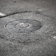 Sewer manhole cover on asphalt road with white road marking — Stock Photo