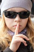 Little girl in sunglasses shows silence sign — Stock Photo