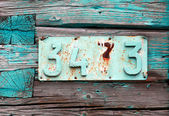 Rusted house number on grunge green wooden wall — Stock Photo