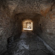 Stock Photo: Old stone fortress dark stone tunnel perspective with glowing end