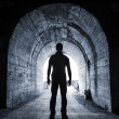 Young man stands in dark tunnel and looks in the glowing end — Stock Photo #29871959