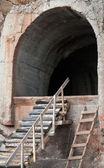 Dark portal of old concrete tunnel in the rock — Stock Photo