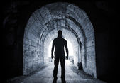 Young man stands in dark tunnel and looks in the glowing end — Stock Photo