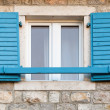 Wooden window with blue open jalousies in old gray stone wall — Stock Photo #29931389