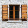 Wooden window with open jalousies in old gray stone wall — Stock Photo #29931483