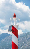 Rad and white striped lighthouse above cloudy sky. Central pier of Perast town, Montenegro — Stock Photo