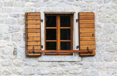 Wooden window with open jalousies in old gray stone wall — Stock Photo
