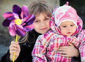 Two Little sisters outdoor portrait with pinwheel toy — Stockfoto