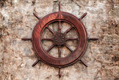 Old wooden ship steering wheel on stone wall — Stock Photo