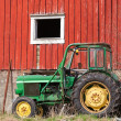 Small green tractor stands on grass nearby red barn wall in Norway — Stock Photo