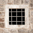 Ancient stone prison wall with metal window bars — Stock Photo