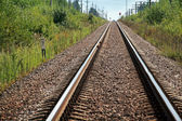 Straight modern railway perspective with gravel, poles, green grass and trees — Stock Photo