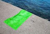 Empty green cotton towel lays on gray concrete pier — Stock Photo