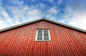Red wooden wall with window above blue cloudy sky — Stock Photo