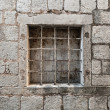 Locked ancient stone prison wall with metal window bars — Stock Photo
