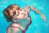 блондинка девочка плавает расслабленным с закрытыми глазами в бассейне — Стоковое фото