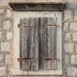 Ancient window with closed wooden jalousies in gray stone wall. Perast town, Montenegro — Stock Photo #30699973