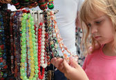 Little blond girl in the souvenir market considers colorful stone beads — Stock Photo