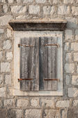 Ancient window with closed wooden jalousies in gray stone wall. Perast town, Montenegro — Stock Photo