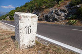 White kilometer stone post on the roadside in Montenegro — Stock Photo