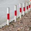 Striped red and white signal poles stand on asphalt roadside — Stock Photo