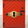 Old red wooden door with lock and large keyhole, old fashioned safety concept — Stock Photo #31150083