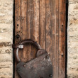 Ancient locked wooden door and big rusted padlock, old fashioned safety concept — Stock Photo #31150087